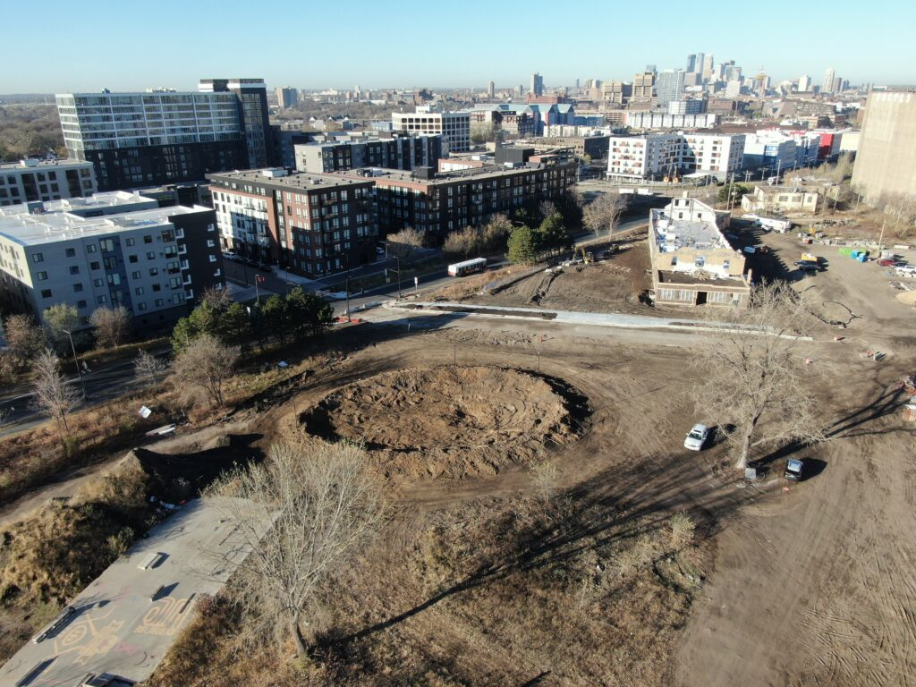 An aerial view of a neighborhood centered on a large empty space with a convex mound of exposed dirt