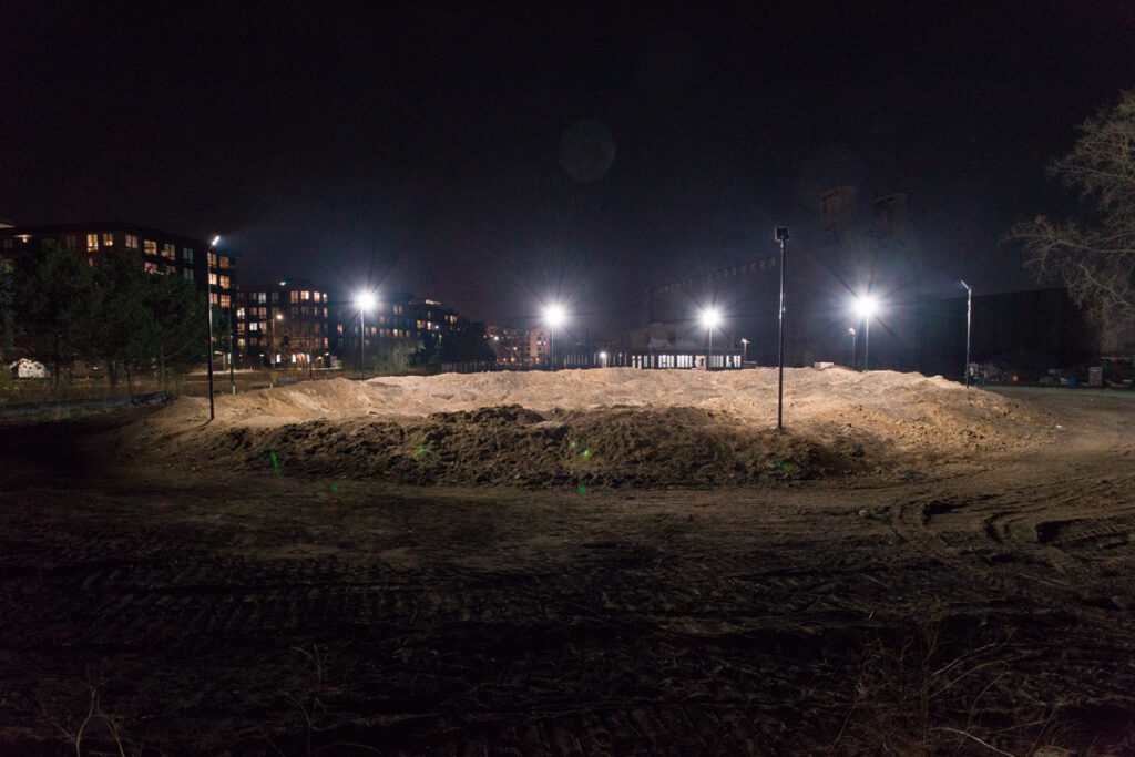 A large convex mound of dirt lit up at night with stadium lights