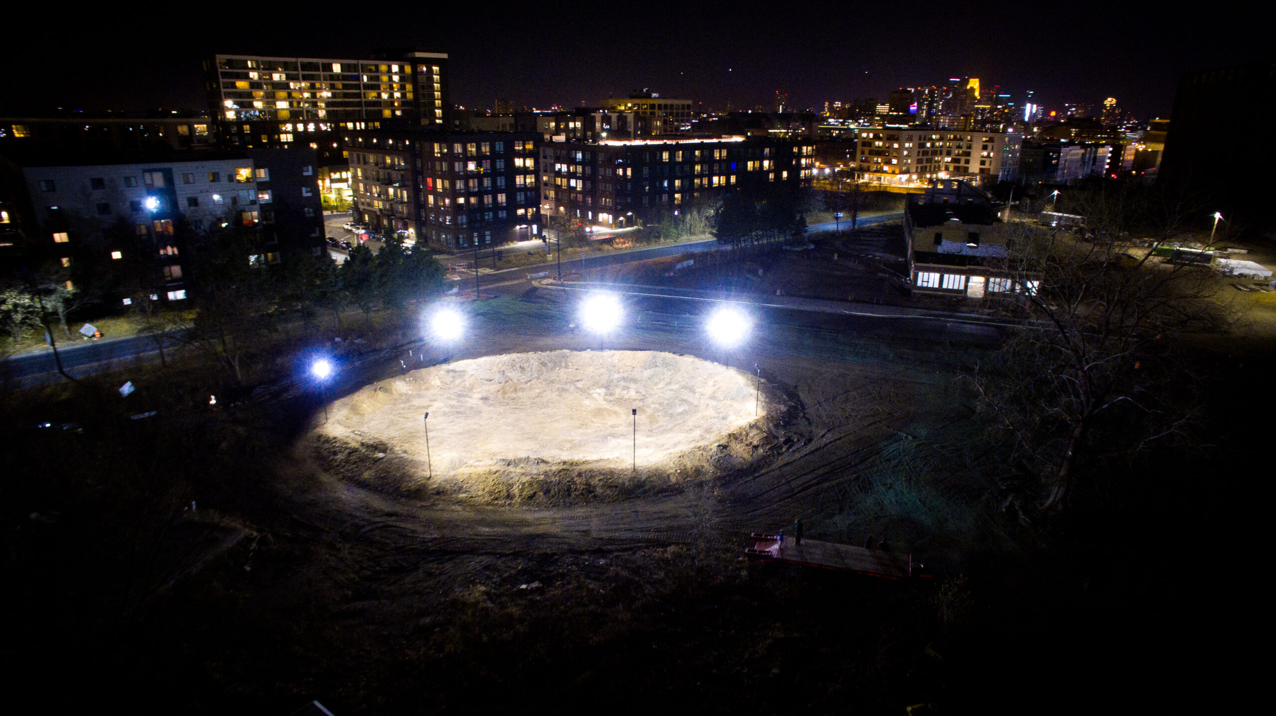 Aerial view of a convex mound of dirt lit with stadium lights at night, with apartment buildings in the background