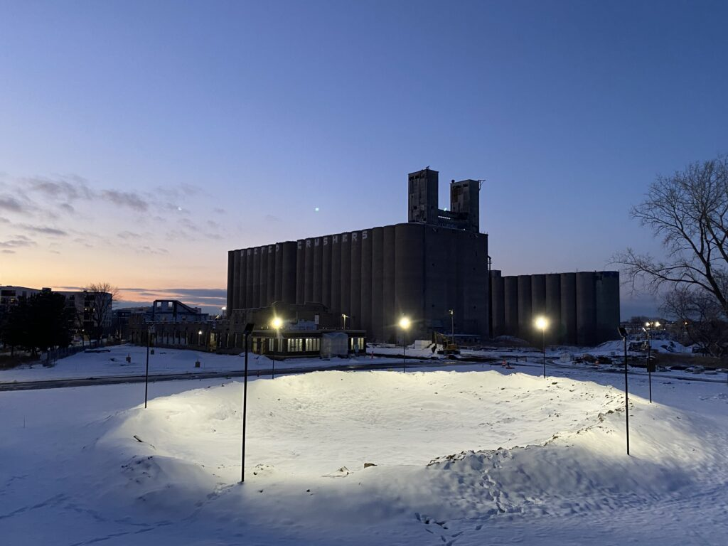 A convex mound covered in snow, lit with stadium lights with a large grain storage building and some other residential structures in the background