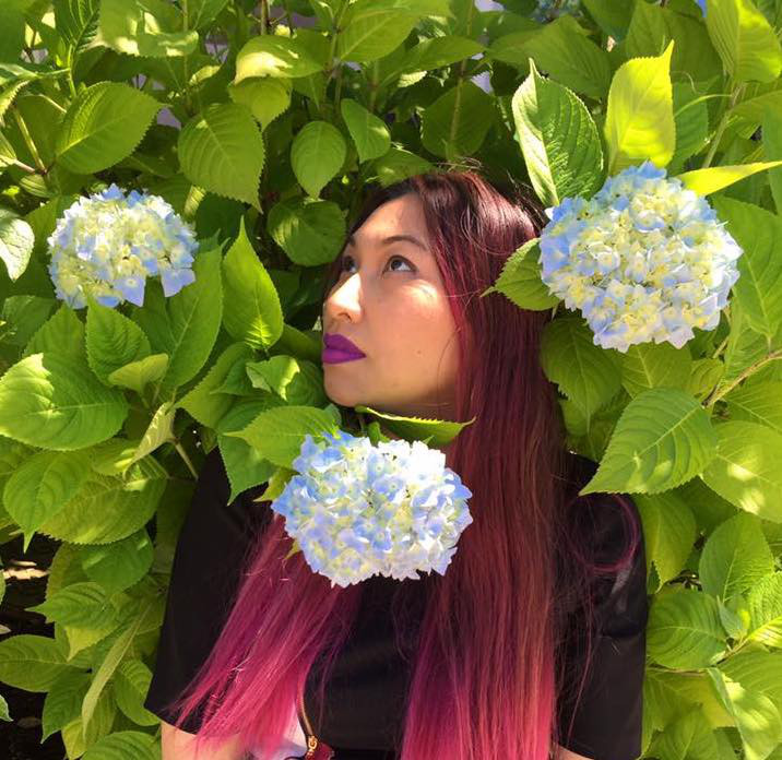 A light skinned woman with long pink hair is standing in a bush with blue hydrangea flowers around her face