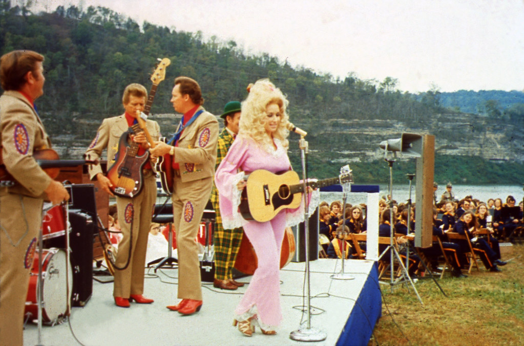 Dolly Parton stands on a stage in front of a microphone with a guitar, wearing a pink jumpsuit. Men in decorative brown suits are behind her on the stage by instruments, an audience is sitting in chairs behind them, and a body of water and green mountains are in the background.