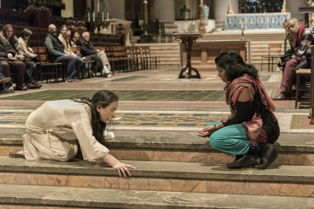 Photo of two women sitting on the stairs of a cathedral, one woman dark-skinned who is draped in a colored shawl reaching her hands out on her lap as she gazes at the other woman, who is draped white and crouching on the stairs. People are witnessing behind them.