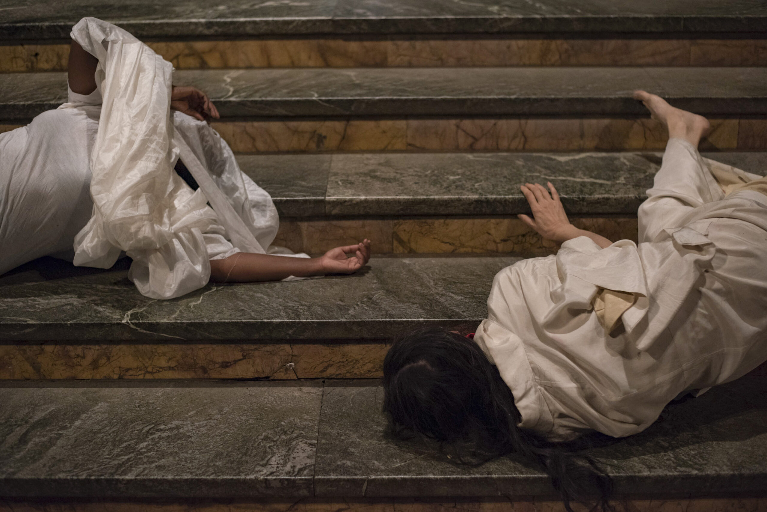 Photo of two women draped in white fabric rolling down the stairs of Cathedral of St. John the Divine.