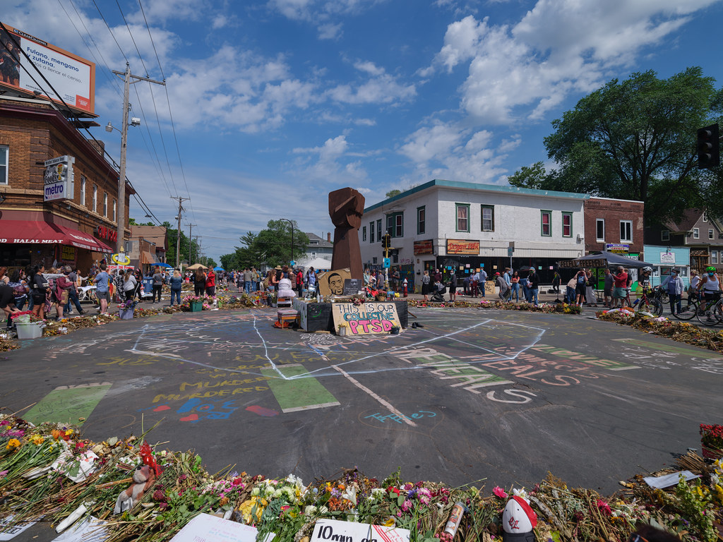 An intersection with a memorial for George Floyd at the center that has a large sculpture of a fist in the air. Signs and flowers are arranged in a circle around the memorial, and people can seen standing on the outside looking in