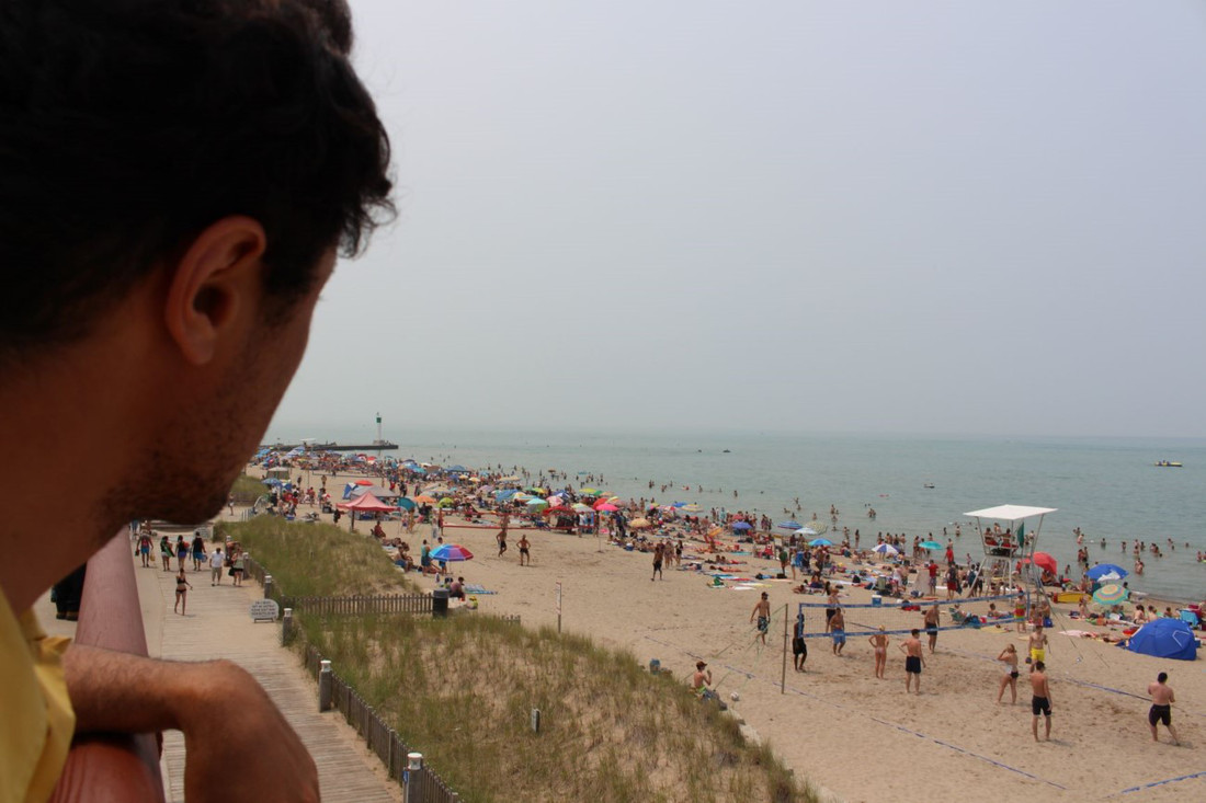 A person is on the left of the frame, appears to be looking out on a beach with people from someplace above the ground