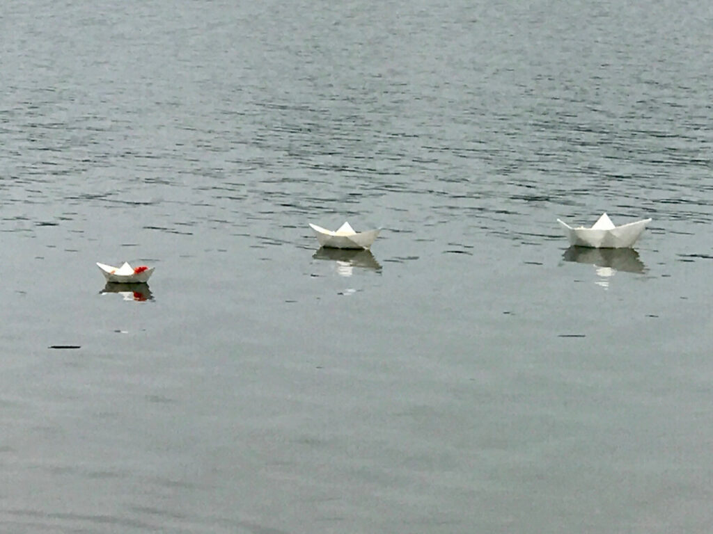 Three white paper boats float on rippling water.