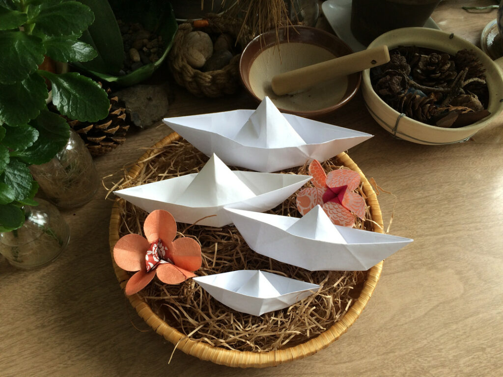 Four white paper boats are arranged in a wicker basket, surrounded by paper flowers, plants, jars, bowls, and pinecones.