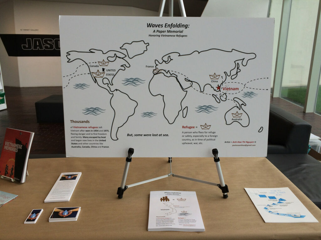 Papers are displayed on a table, including a large world map depicting routes of Vietnamese refugees.