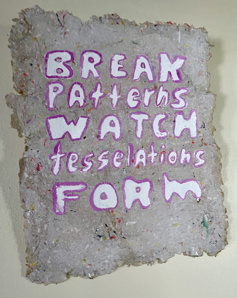 """Handmade paper in grey flecked with color in an uneven square, broken edges. """"BREAK PATTERNS WATCH tesselations FORM"""" is painted on it."""