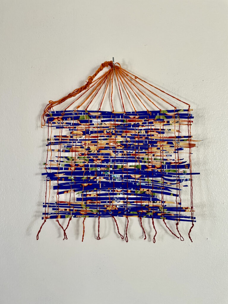 A weaving is hung on a wall, orange string interwoven with small fragments from the packaging of clementines