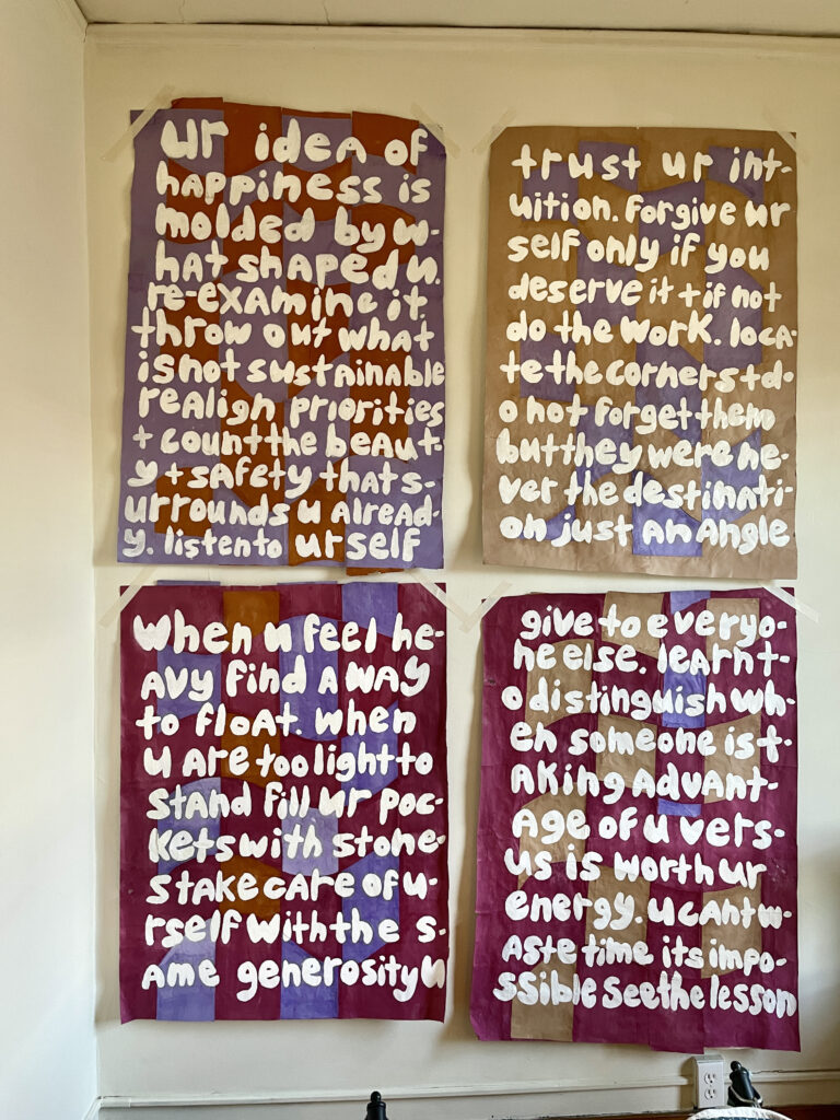 4 multicolored papers are featured against the wall and read affirmations written in white gouache