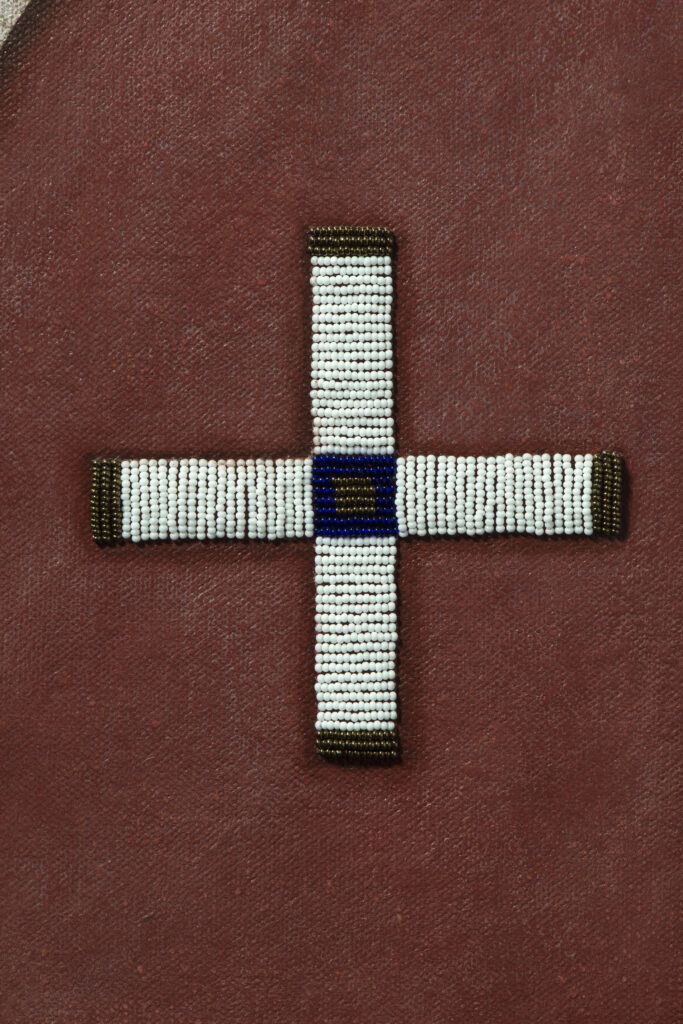 Beaded cross pattern stitched onto red background.