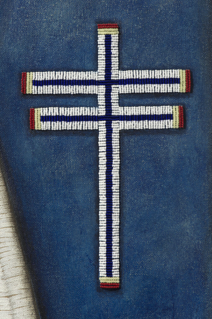 Beaded white cross pattern stitched onto blue background.