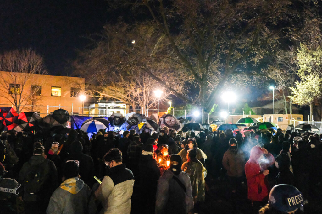 A crowd of protesters with masks, umbrellas, and candles, under a tree, street lights, and night sky.