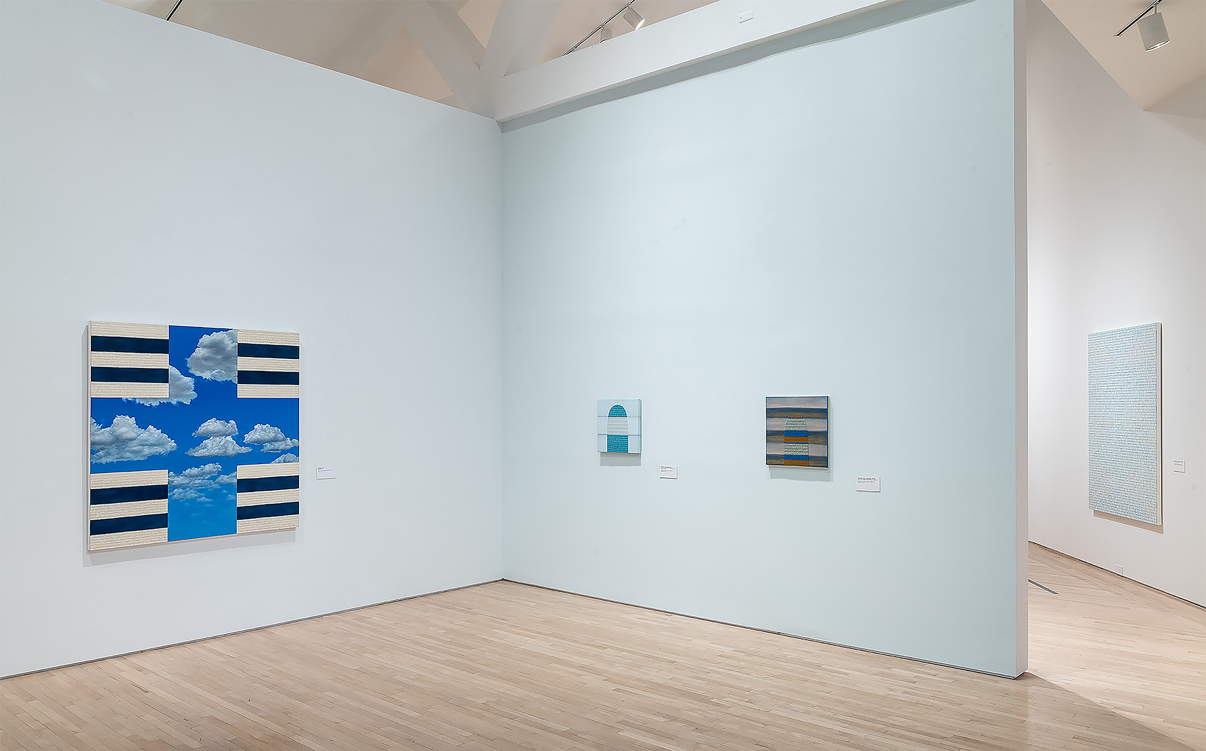 Abstract paintings in white-walled gallery.