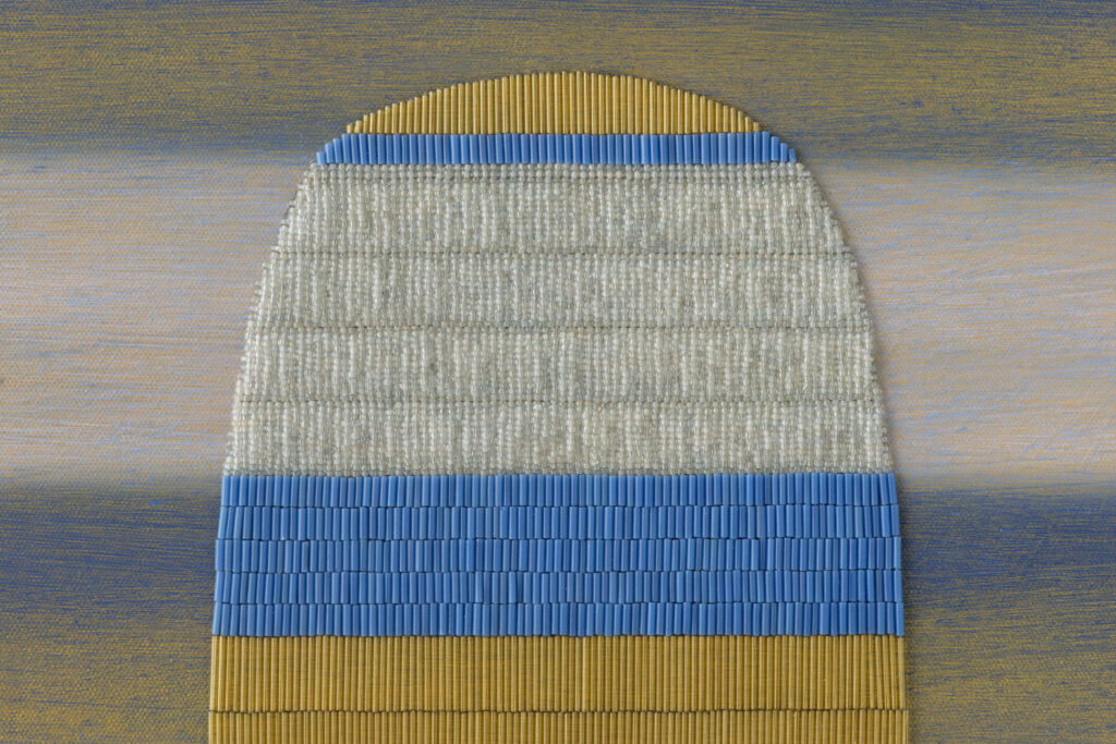 Detail of blue, yellow, and white striped painting with oblong beaded shape.