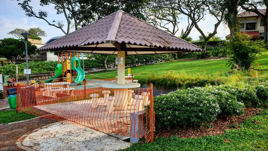 An outdoor playground is blocked by orange plastic webbing material