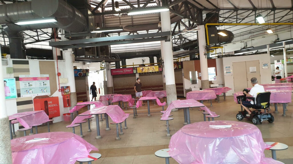 An indoor cafeteria is pictured with many tables, each table covered with pink plastic sheeting