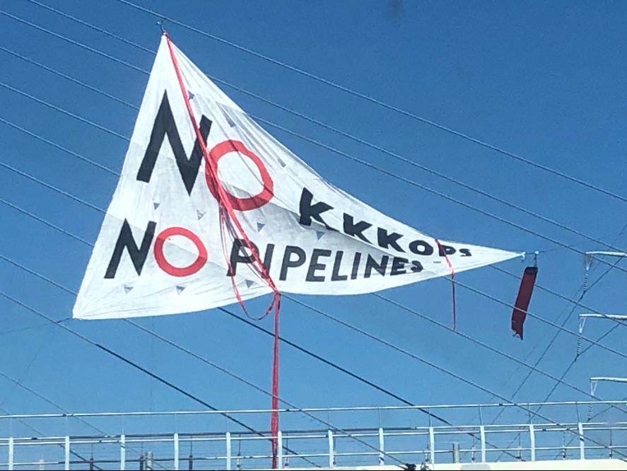 Triangular banner against blue sky reads: NO KKKOPS / NO PIPELINES.