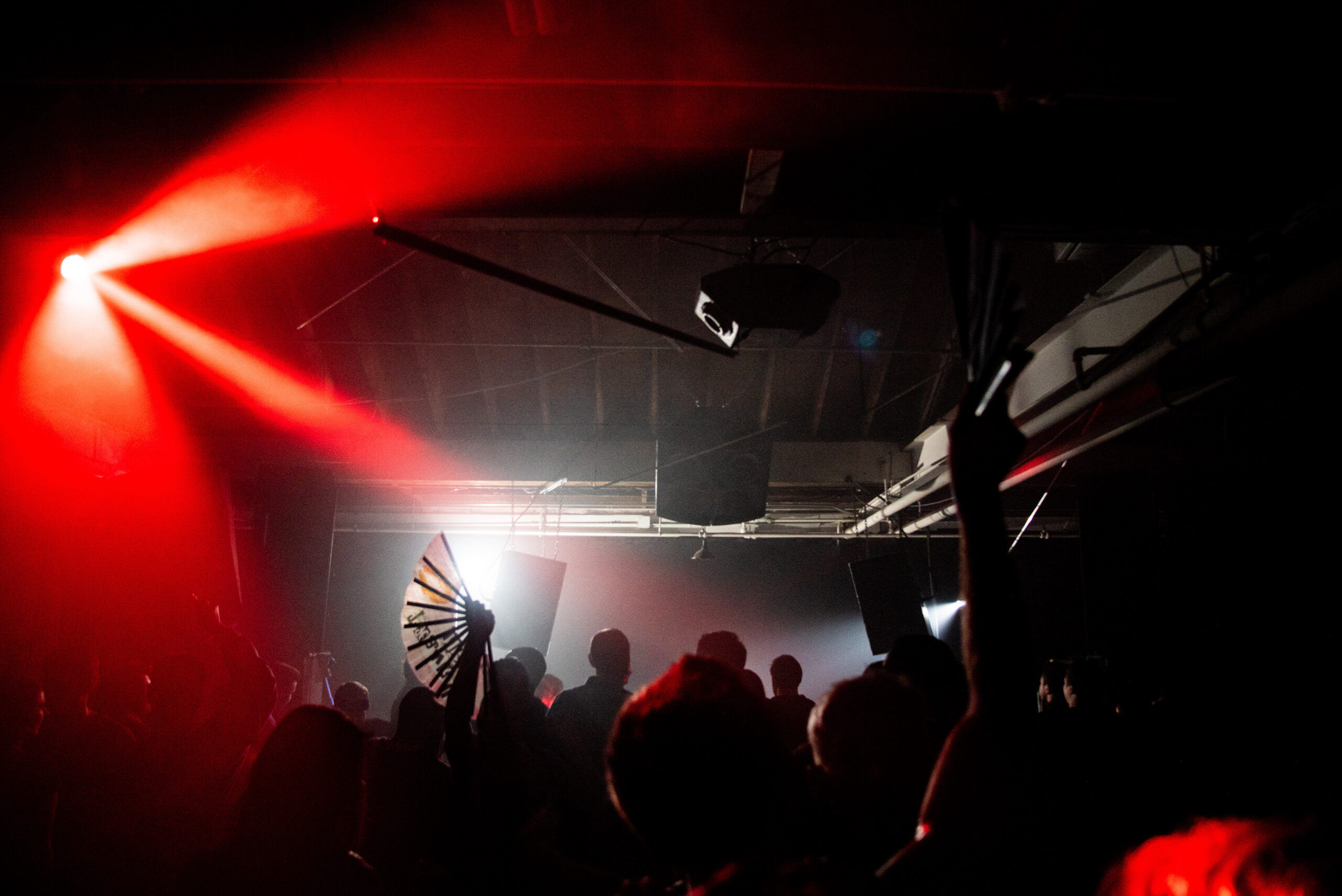 Three beams of red light over a crowd on a dark dance floor, and a white fan raised above the crowd.