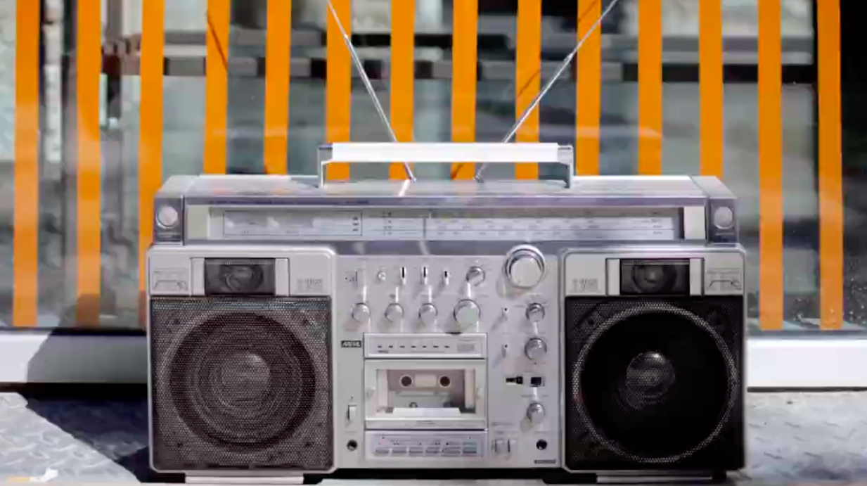 Silver boom box in front of background with vertical orange stripes.