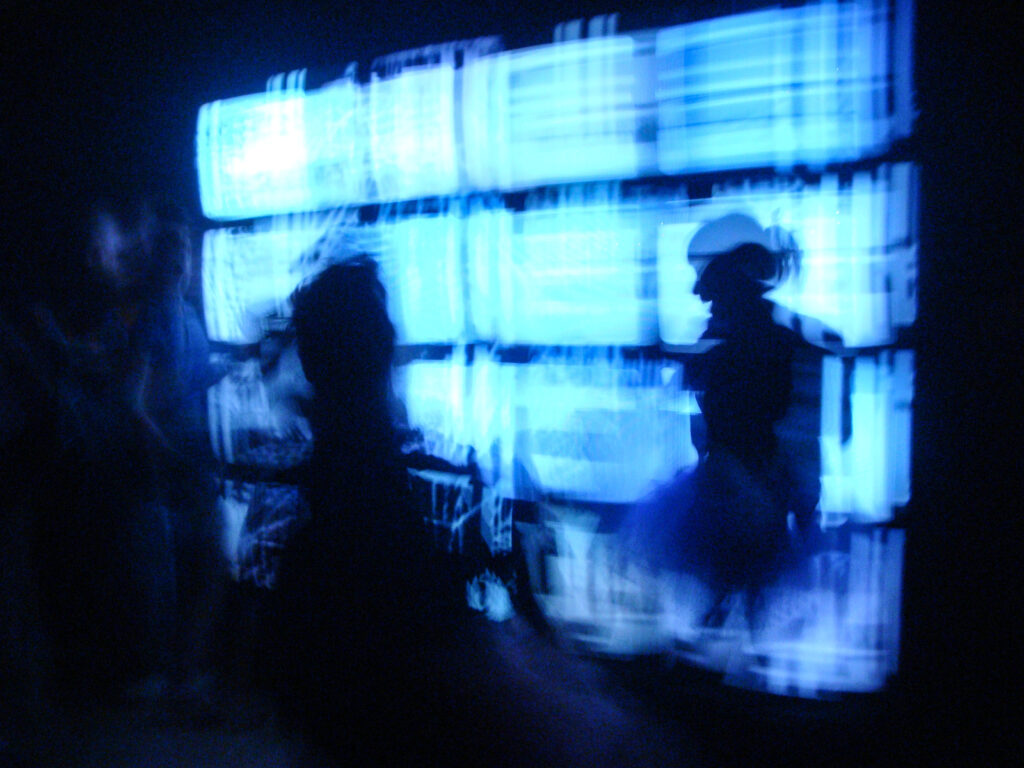 Blue light from a bank of TV screens, with silhouettes of two people.
