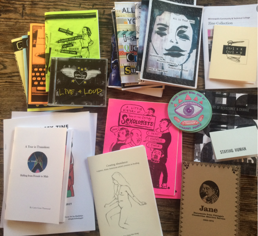 Many zines in neon colors spread out on a surface, with a prominent drawing of a face.