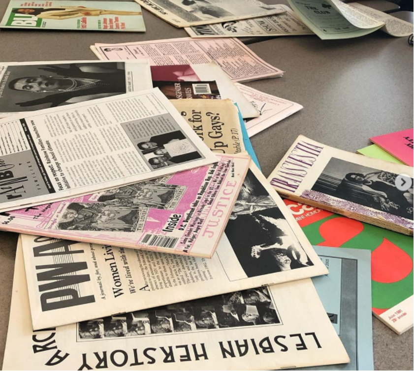 Collection of newspapers and zines, with a headline reading: LESBIAN HERSTORY.