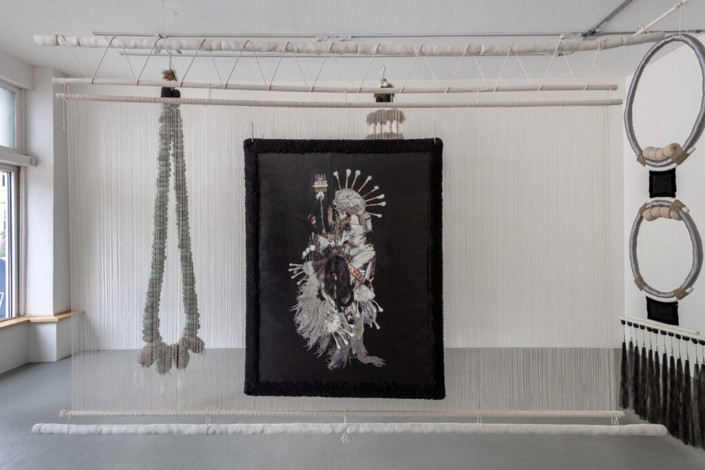 Installation view of hanging fiber sculptures and a large print of a figure with black background.
