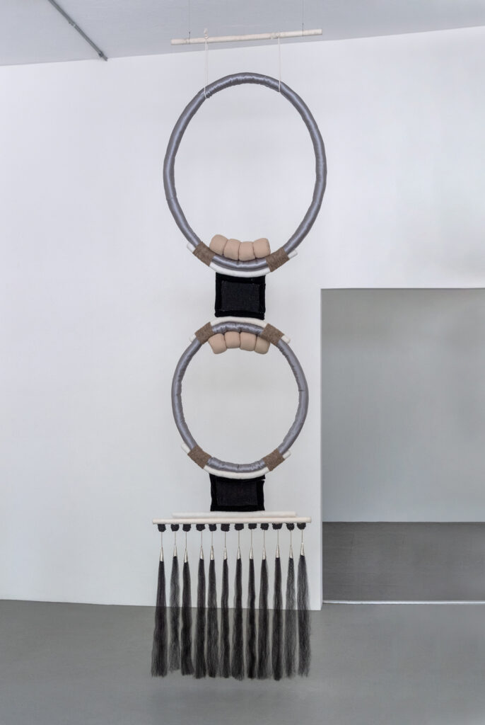 Hanging fiber sculpture with two gray hoops and row of long tassels.