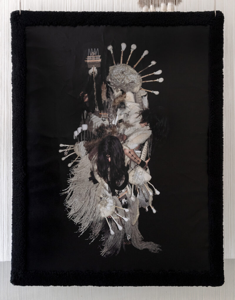 Photograph of a figure wearing a fiber and fur costume against black background.