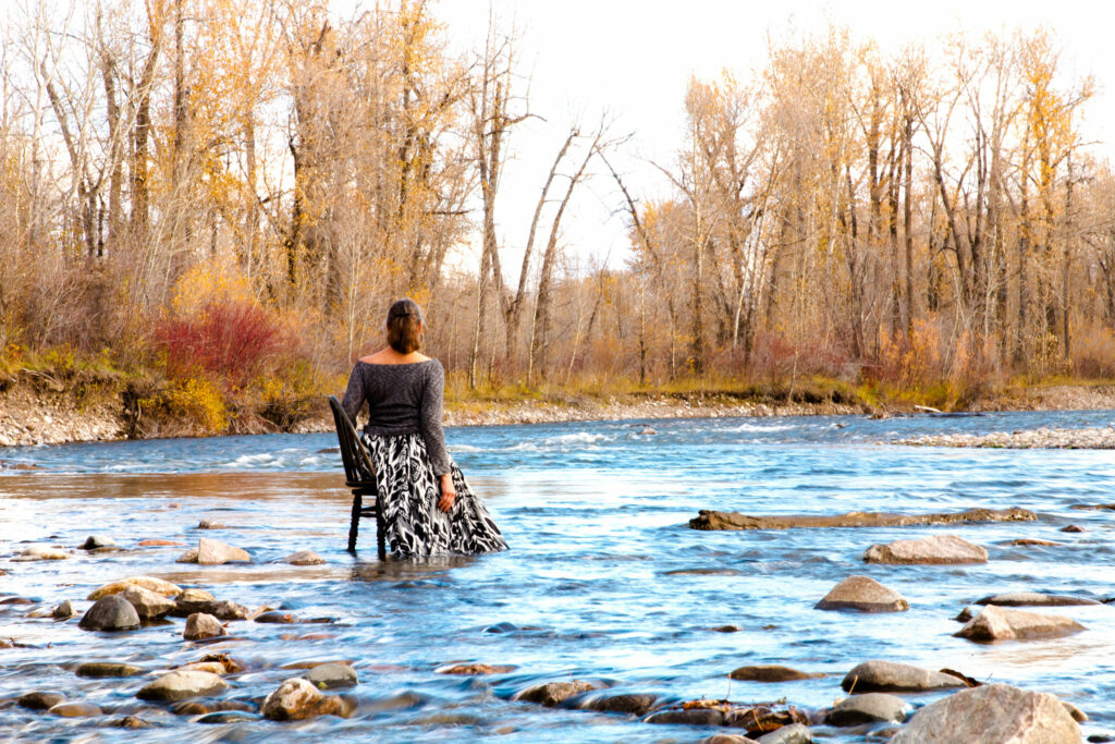 Person wearing a long skirt sits in a chair in the middle of a rocky creek.