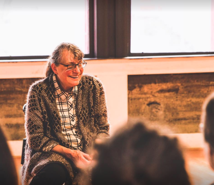 Person with gray ponytail, glasses, plaid shirt and gray sweater sits in front of a window.