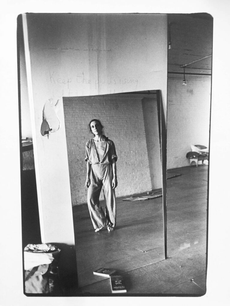 Black and white photo of Mary Overlie, looking into a mirror with heel raised off the ground.