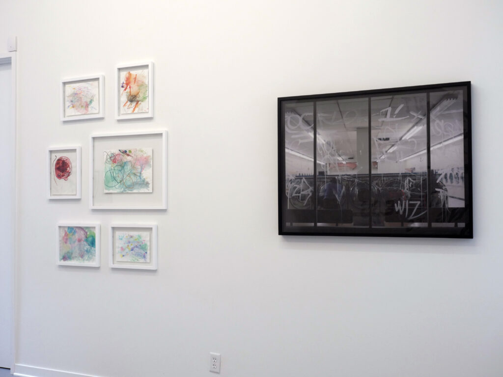 Group of multicolored abstract drawings hung on a white wall, next to a dark grayscale photograph.