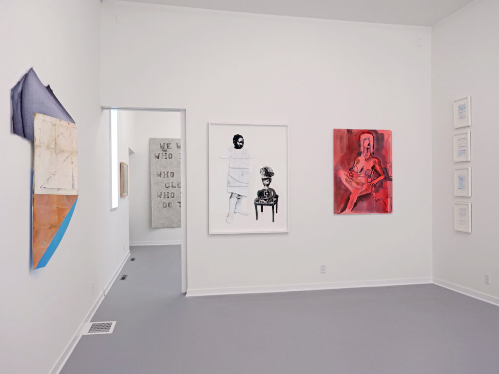 Gallery with gray floors and open doorway, with red, black and white 2D artwork hung on white walls.