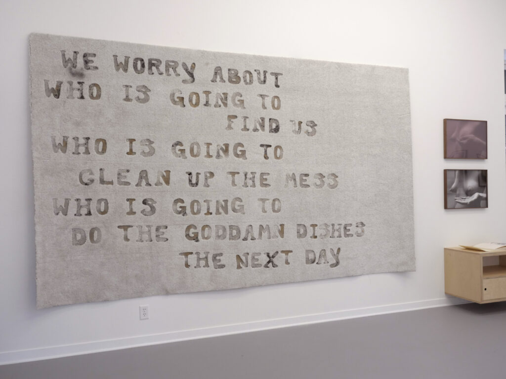 """Beige textile piece hung on white wall, reading: WE WORRY ABOUT / WHO IS GOING TO / FIND US / WHO IS GOING TO / CLEAN UP THE MESS / WHO IS GOING TO / DO THE GODDAMN DISHES / THE NEXT DAY"""""""