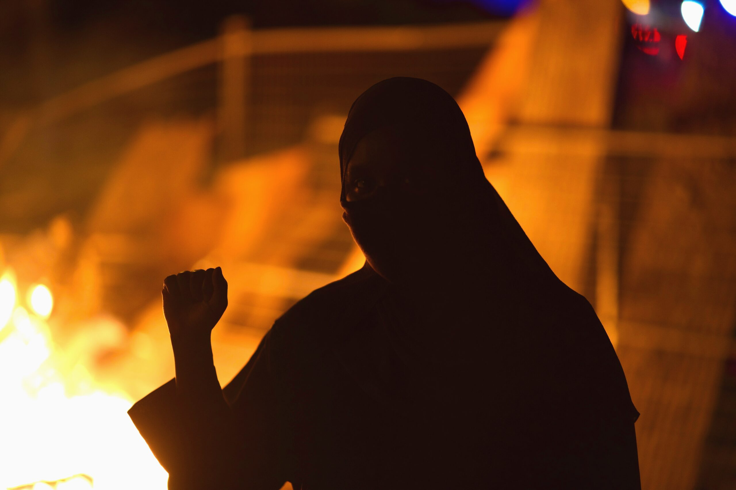 Silhouette of a person with fist raised, with fire glowing in background.