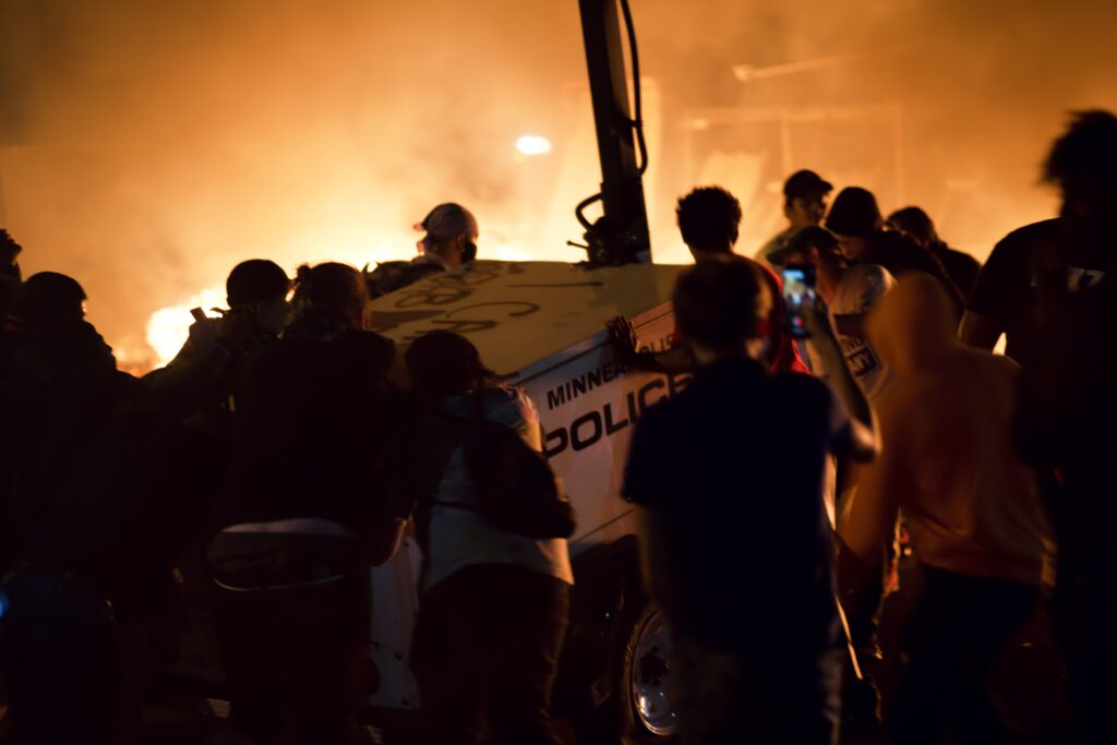 Crowd of people surrounds police mobile surveillance trailer, with fire glowing in background.