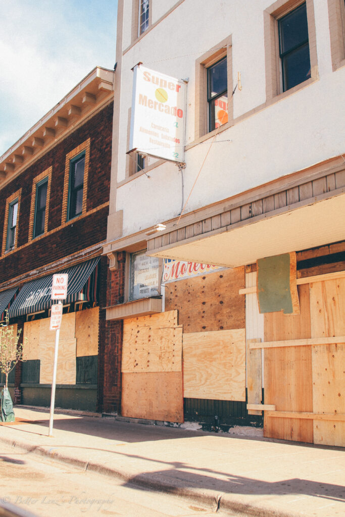 Plywood boards cover storefronts.