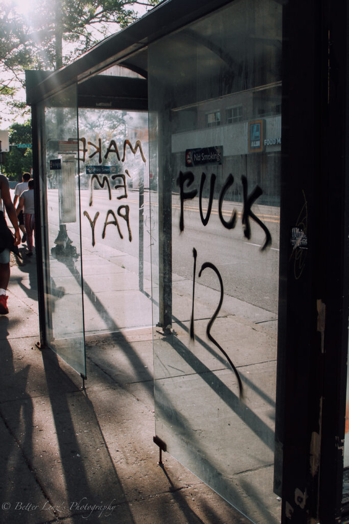 """Light shines through glass bus shelter, with tag reading """"FUCK 12."""""""