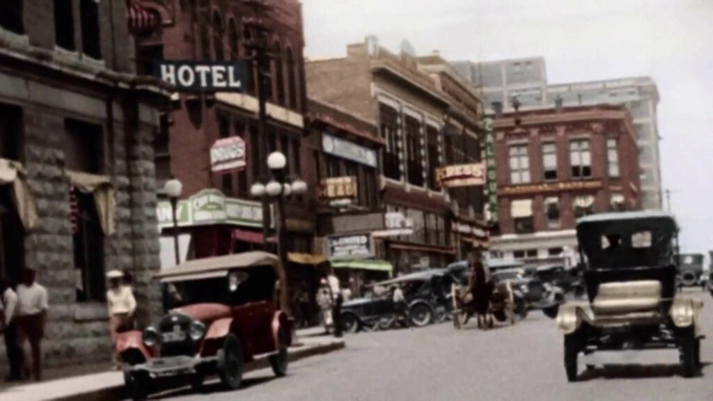 Vintage photograph of busy street scene with cars and brick buildings.