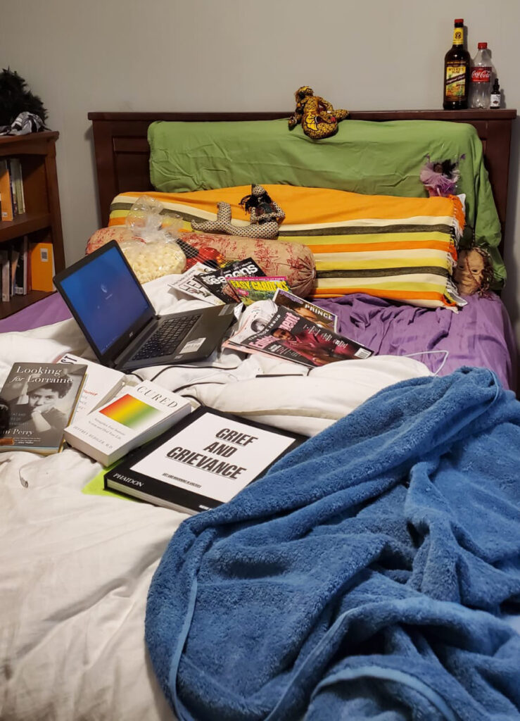 Bed with white duvet, blue towel, purple sheets, green and orange striped pillows, magazines, laptop, and many books.