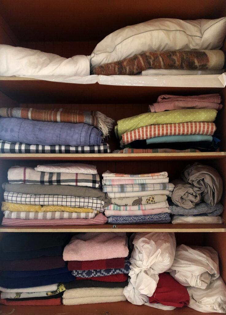 Stacks of folded multicolored textiles arranges on shelves.