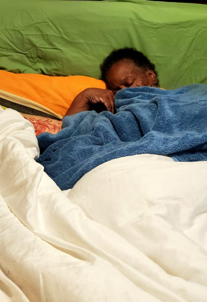 Person with dark skin lays in bed with eyes closed, face covered by blue towel.