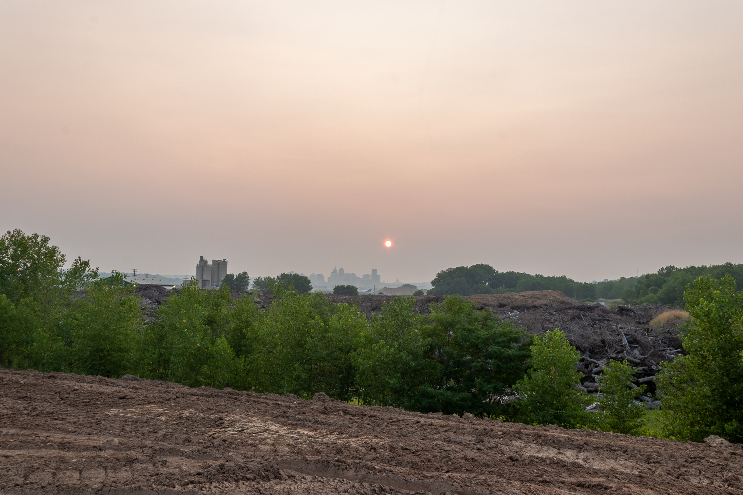 Sun sets over city skyline in hazy pink sky, behind brown dirt with tire tracks and line of green trees.