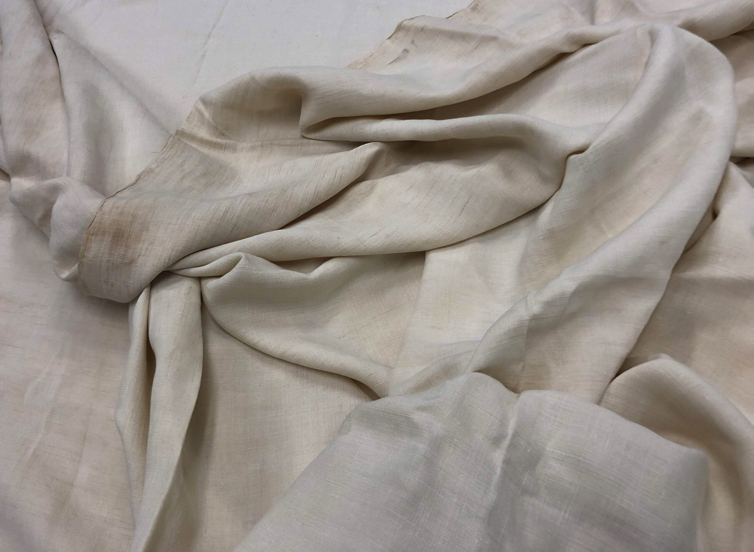 Loosely folded off-white textile.