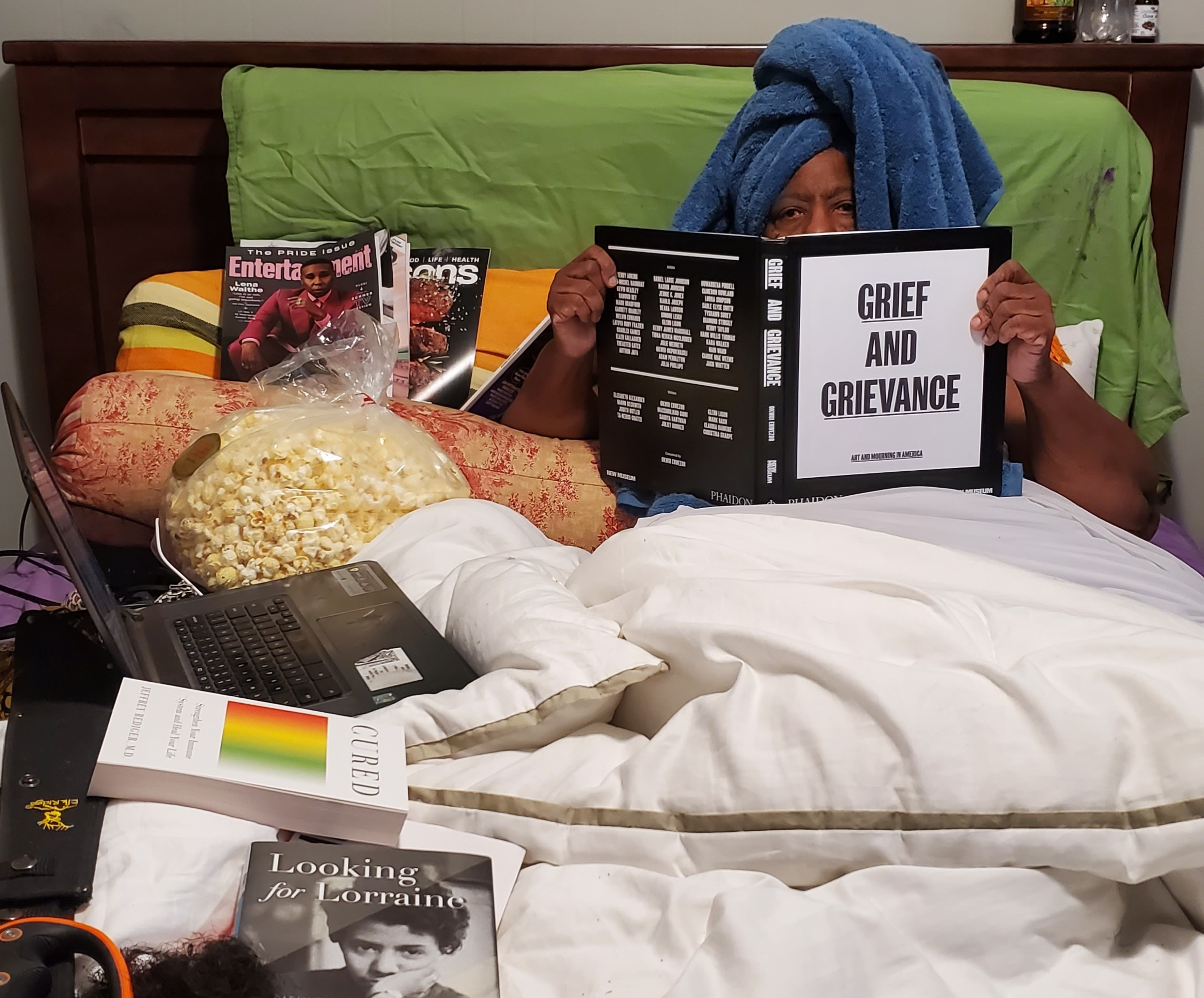 """Person with dark skin and head wrapped in blue towel sits in bed full of books, holding up a book whose cover reads """"GRIEF AND GRIEVANCE."""""""