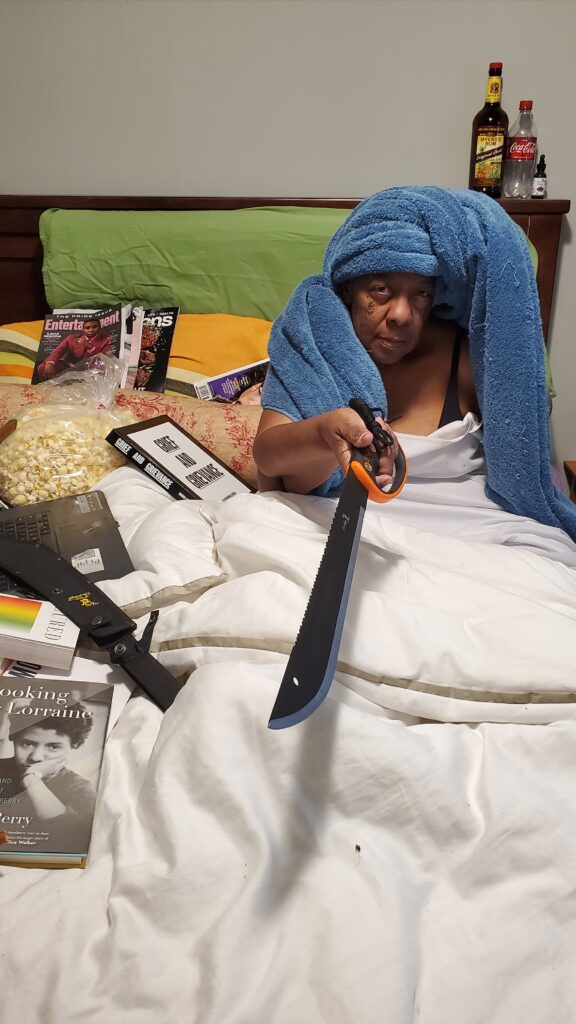 Person with dark skin and head wrapped in blue towel sits in bed covered with books, pointing a machete at the camera.